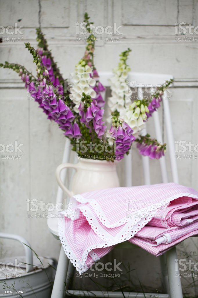 beautiful bouquet of field flowers - foxglove against the background of old white door stock photo