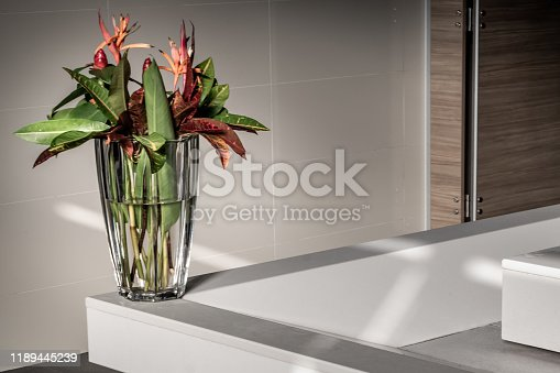 Beautiful bouquet of flowers in a glass vase on a decorative white stone at basin in modern bathroom without people. Bathroom interior., Space for text.