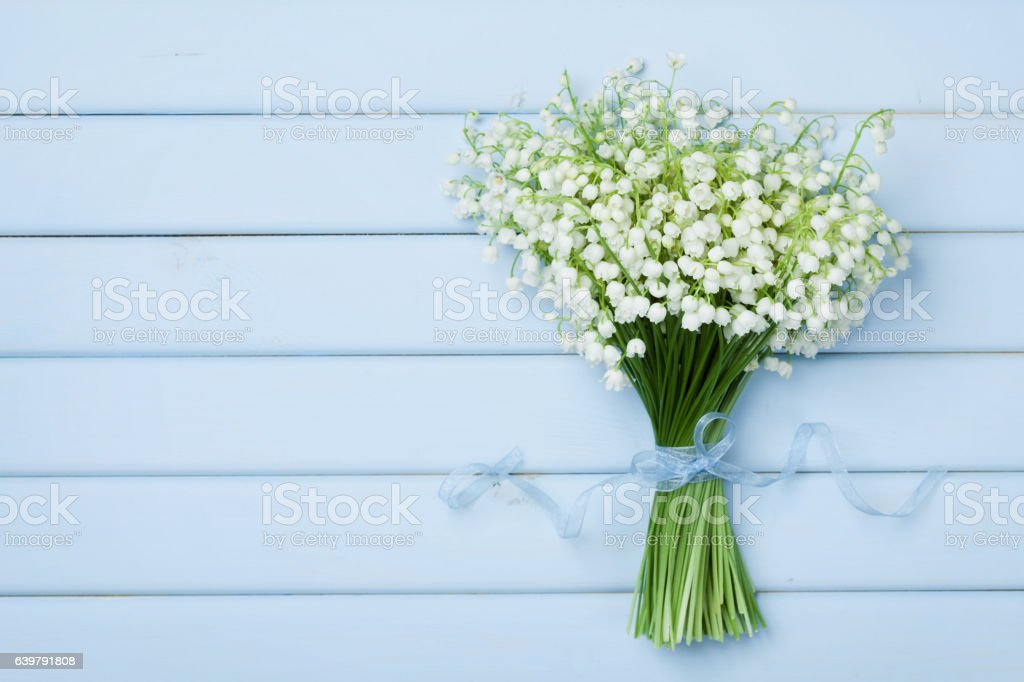 Beautiful bouquet of flowers lily of the valley. Flat lay. stock photo