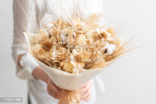 beautiful bouquet of mixed dry flowers in woman hand. the work of the florist at a flower shop. Delicate Pastel tones color.