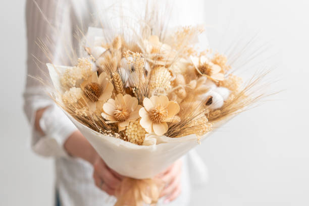beautiful bouquet of mixed dried flowers in woman hand. the work of the florist at a flower shop. Delicate Pastel tones color beautiful bouquet of mixed dry flowers in woman hand. the work of the florist at a flower shop. Delicate Pastel tones color. dried plant stock pictures, royalty-free photos & images