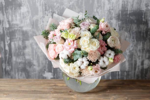 mooi boeket van gemengde bloemen in een vaas op houten tafel. het werk van de bloemist op een bloemenwinkel - bloemstuk stockfoto's en -beelden