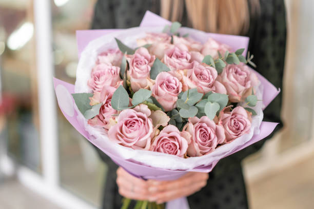 Beautiful bouquet of pastel purple roses in womans hands. the work of the florist at a flower shop. Delivery fresh cut flower. European floral shop. stock photo