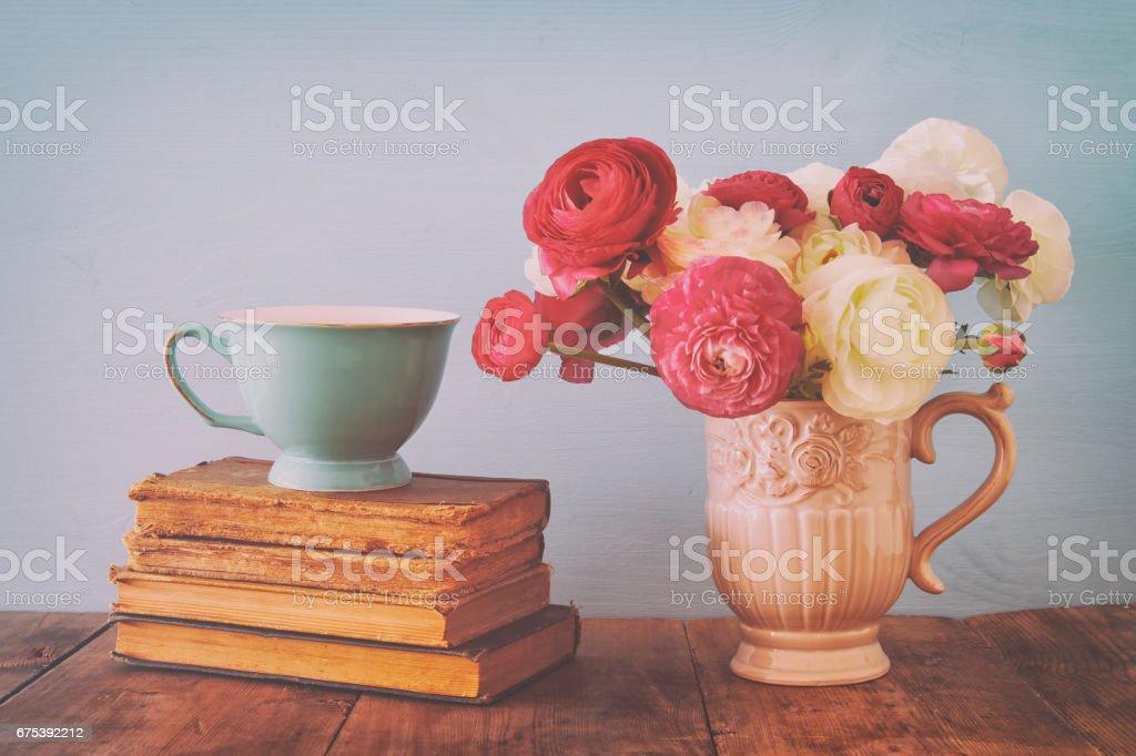 Beau bouquet de fleurs de printemps dans le vase à côté de vieux livres sur la table en bois photo libre de droits