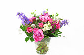 Beautiful bouquet of colorful spring flowers in a vase on white background