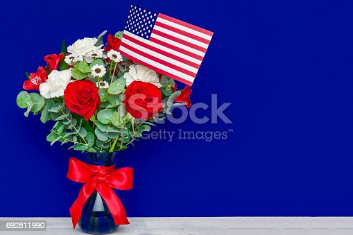 istock Beautiful bouquet with american flag on blue background 692811990
