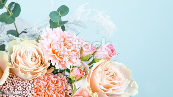 istock Beautiful bouquet with pink carnations and roses close-up on a blue background. 1134225564