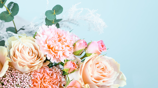 Beautiful bouquet with pink carnations and roses close-up on a blue background.