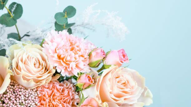 mooi boeket met roze anjers en rozen close-up op een blauwe achtergrond. - boeket stockfoto's en -beelden