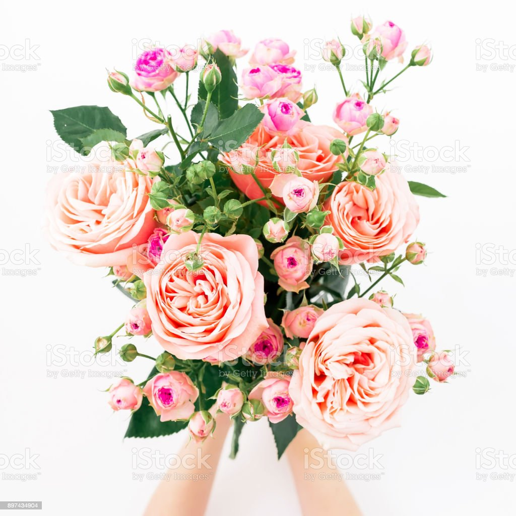 Cтоковое фото Beautiful bouquet with pink roses in hands on white background. Flat lay, top view. Valentines day composition