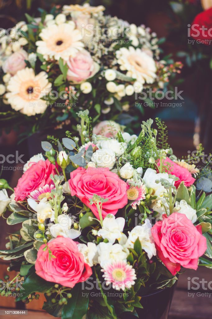 Beautiful bouquet with pink roses on a showcase in a French shop outside. stock photo