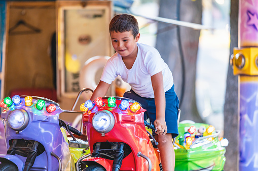 Beautiful boy having fun on the ride at the local carnival
