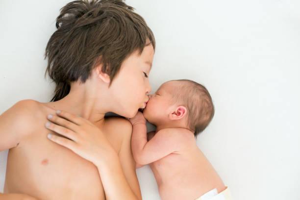 Beau garçon, embrassant avec tendresse et des soins de son frère nouveau-né à la maison - Photo