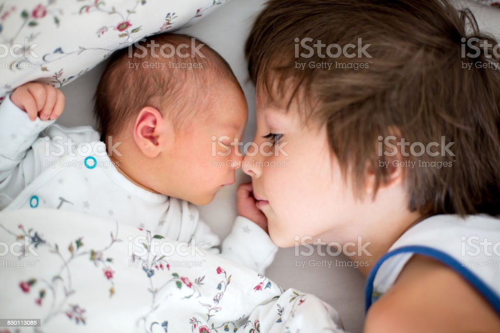 Beautiful boy, hugging with tenderness and care his newborn baby brother at home stock photo