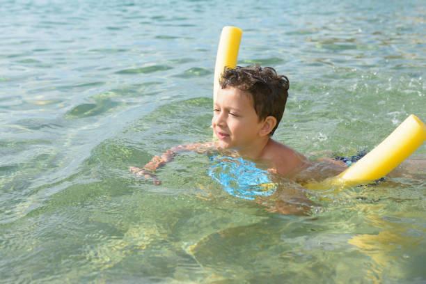 Schöne junge mit Nudel-Schwimmer schwimmen lernen – Foto
