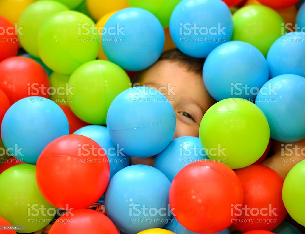 Beautiful Boy Playing in a Colorful Ball Pit in Playground stock photo