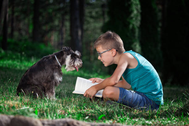Beautiful boy reading a book with his best friend-dog People and pats. Dog. Children.Very Shallow DOF. Developed from RAW; retouched with special care and attention; Small amount of grain added for best final impression. 16 bit Adobe RGB color profile. designer baby stock pictures, royalty-free photos & images