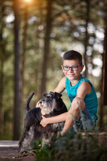 Beautiful boy with his best friend-dog People and pats. Dog. Children.Very Shallow DOF. Developed from RAW; retouched with special care and attention; Small amount of grain added for best final impression. 16 bit Adobe RGB color profile. designer baby stock pictures, royalty-free photos & images