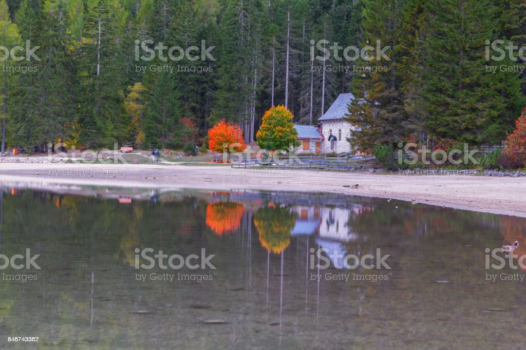 Beautiful Braies lake and church in the background of pine forests stock photo