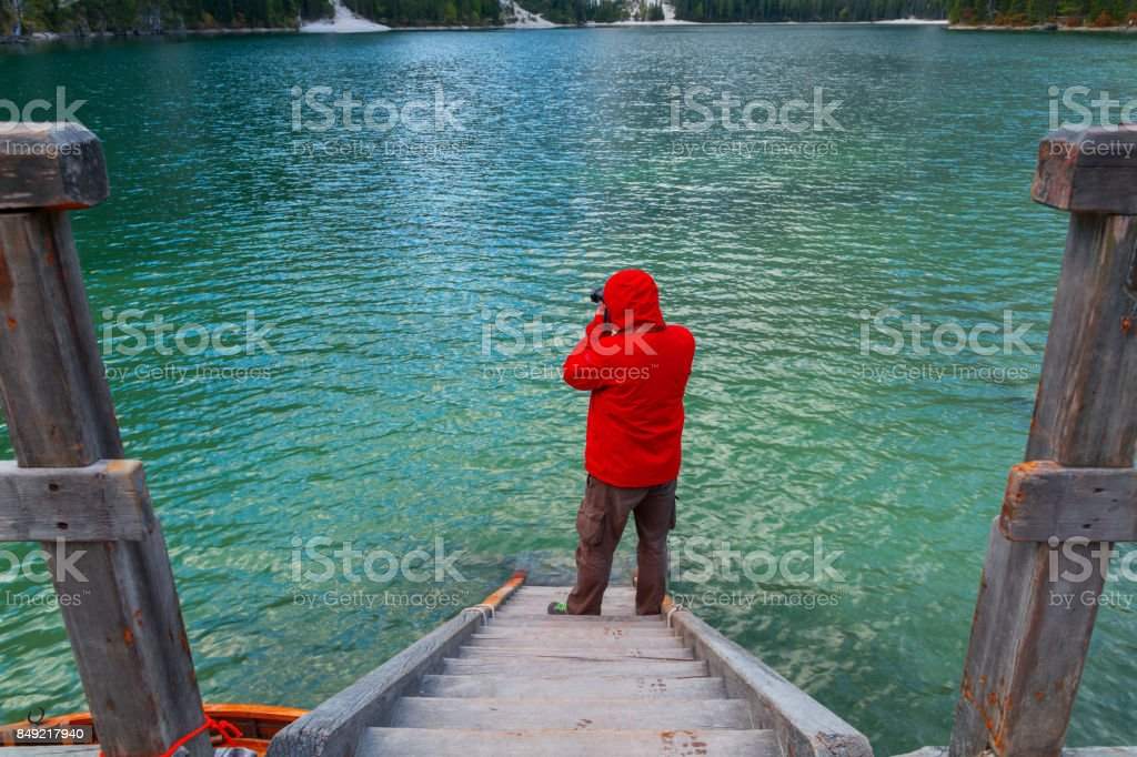 Beautiful Braies lake and the lonely man in the background of Seekofel mountain stock photo