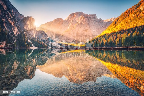 istock Beautiful Braies lake at sunrise in autumn in Dolomites, Italy. Landscape with mountains, gold sunlight, water with reflection, trees with orange leaves in fall morning. Travel in italian alps. Nature 1089320910