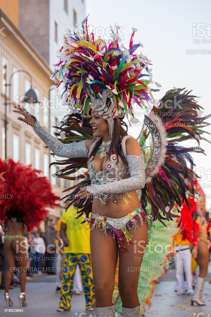 Beautiful Brazil Lady dancing Samba on the streets of city carnival,...