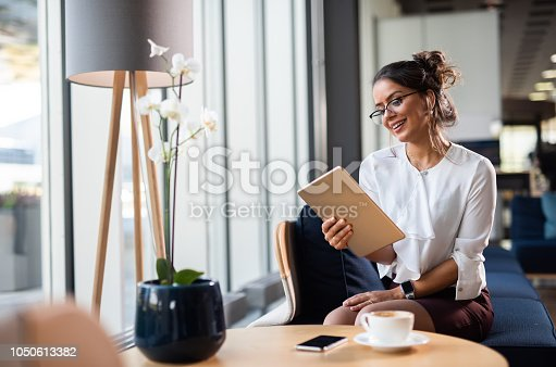 912944158istockphoto Beautiful Brazilian businesswoman working on iPad. 1050613382