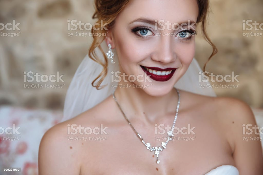 A beautiful bride and a dress with open shoulders. A close-up shot of a girl with a delicate eye makeup and red lips smiles. Light curls of hair, earrings and a thin necklace emphasize the neck zbiór zdjęć royalty-free