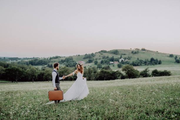schöne braut und bräutigam bei sonnenuntergang in der grünen natur. - hipster braut stock-fotos und bilder