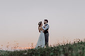 Young bride and groom outside in green nature at romantic sunset, hugging.