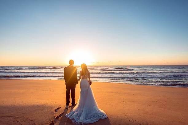 wunderschöne braut und bräutigam am strand - romantische strand fotos stock-fotos und bilder