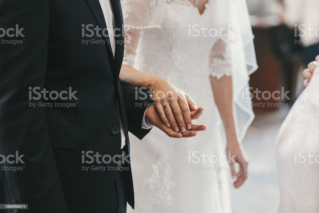 beautiful bride and groom hands exchanging wedding rings in church during wedding ceremony. spiritual holy matrimony. wedding couple and priest putting on rings stock photo