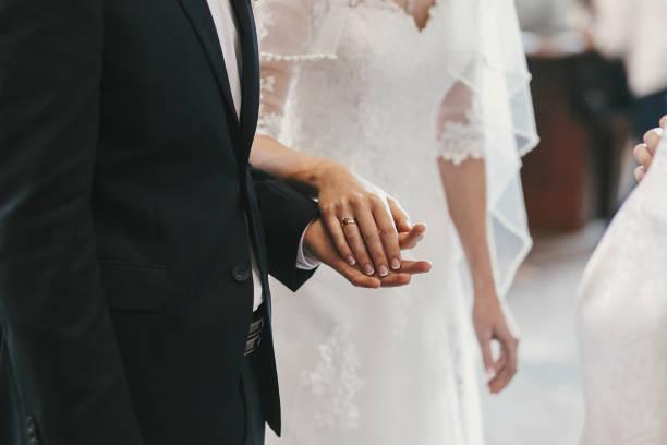 schöne braut und bräutigam hände, die austausch von trauringe in der kirche während der trauung. spirituellen heiligen ehestand. hochzeitspaar und priester, die ringe aufsetzen - altar stock-fotos und bilder