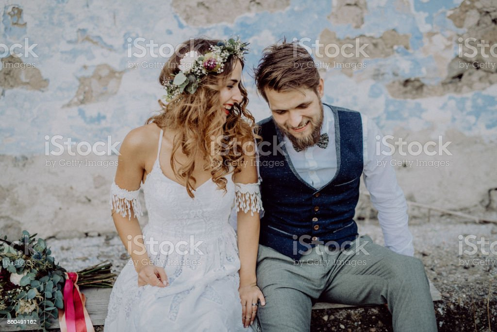 Beautiful bride and groom in front of old shabby house. stock photo