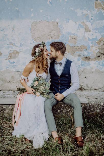 schöne braut und bräutigam vor alte schäbige haus. - hipster braut stock-fotos und bilder