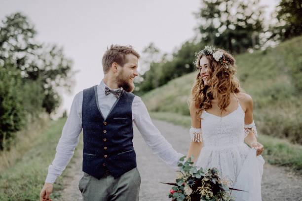 schöne braut und bräutigam in der grünen natur, hand in hand. - hipster braut stock-fotos und bilder