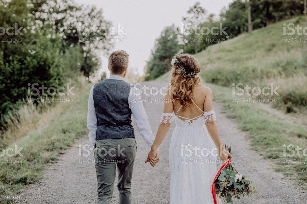 Belle mariée et le marié dans une nature verdoyante, main dans la main. - Photo