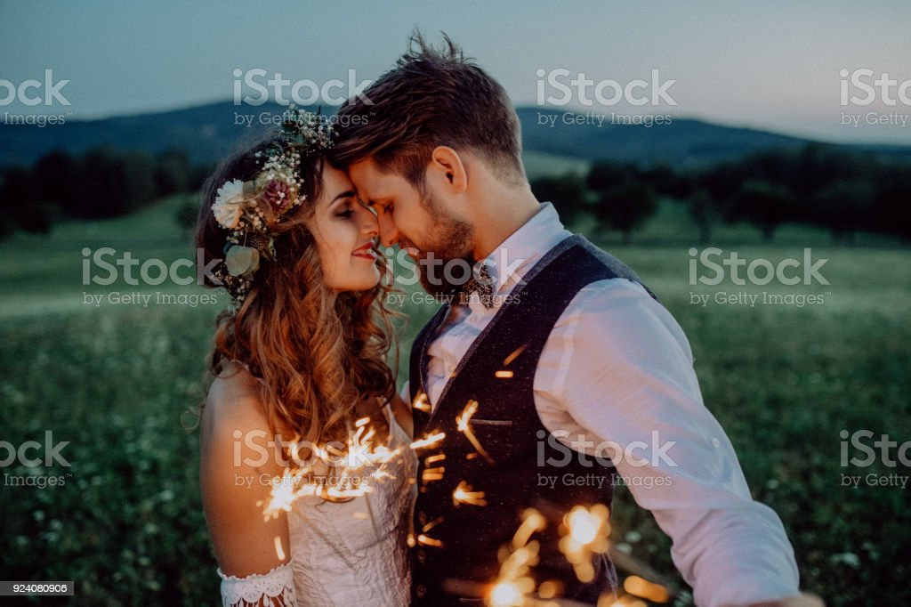 Beautiful bride and groom with sparklers on a meadow. stock photo