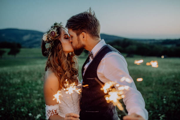 beautiful bride and groom with sparklers on a meadow. - wedding stock photos and pictures