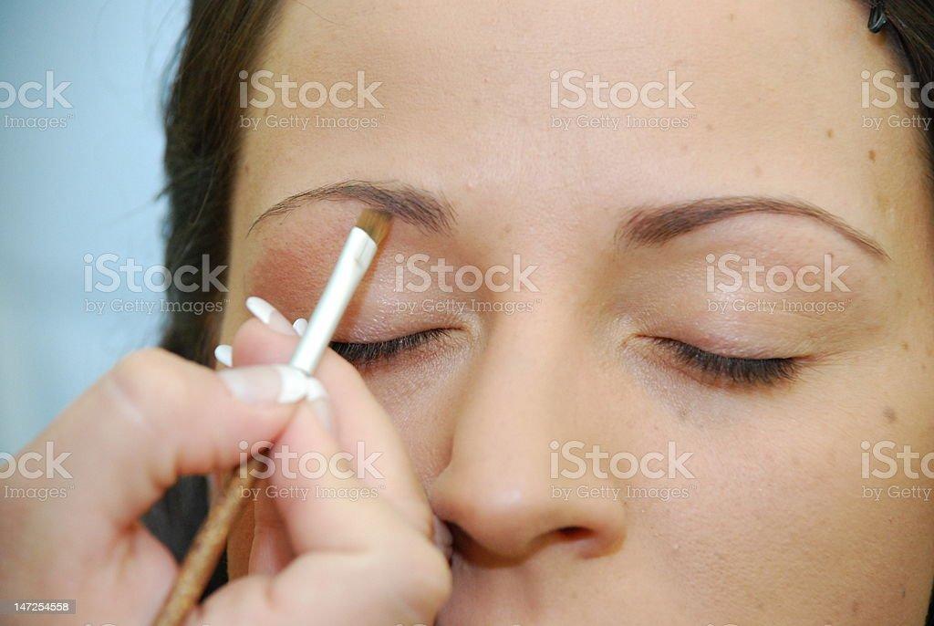 Beautiful bride applying makeup stock photo