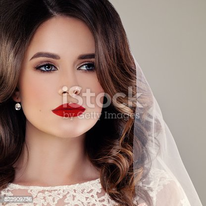 istock Beautiful Bride Fashion Model, Closeup Wedding Portrait. Woman Fiancee with Curly Hairstyle and Event Makeup 823909736
