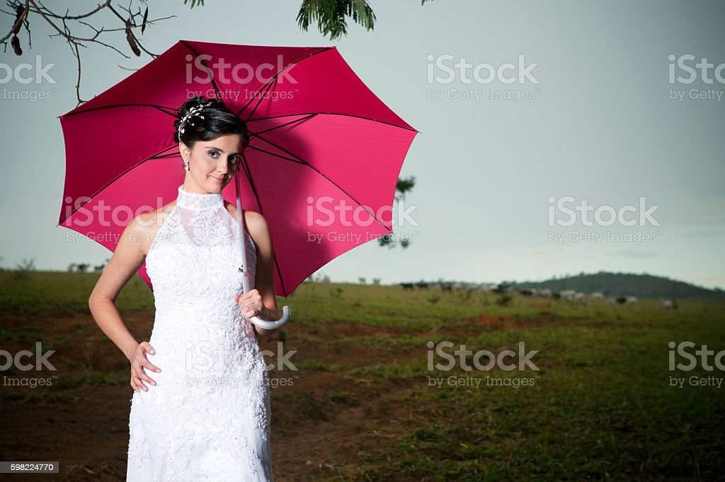Beautiful Bride Holding a Pink Umbrella in a Farm Outdoors foto royalty-free