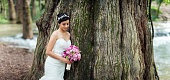 Beautiful bride holding bouquet and leaning on tree