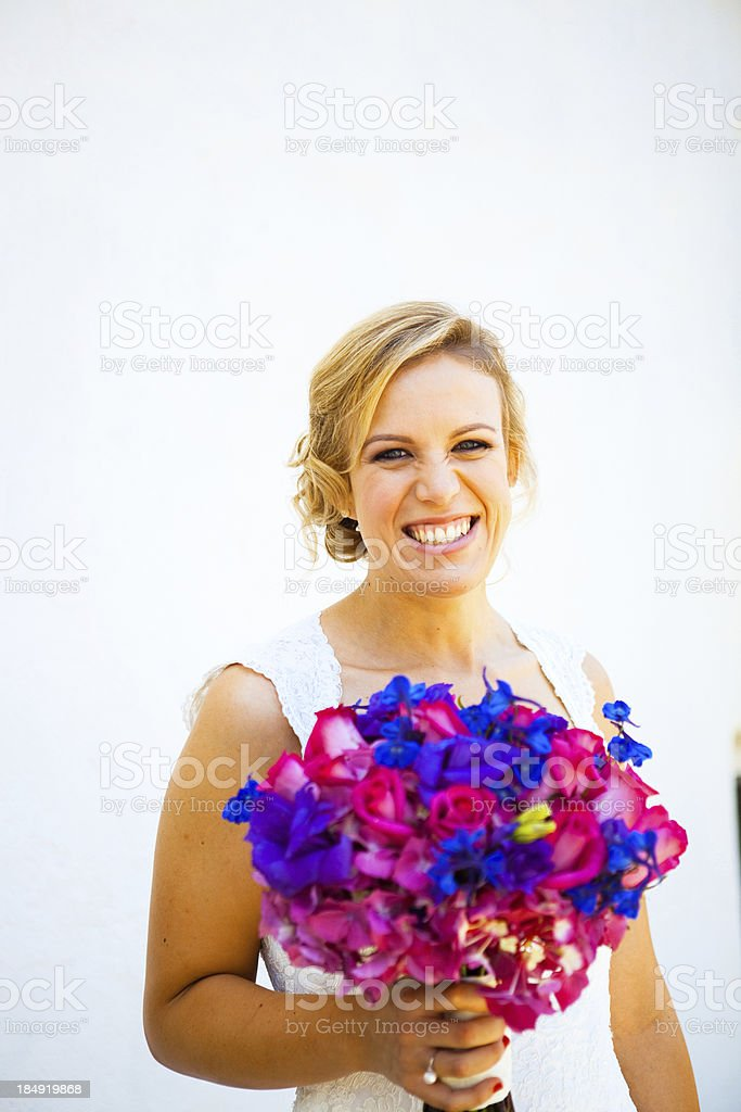 Beautiful bride holding bouquet of blue and pink flowers wedding royalty-free stock photo