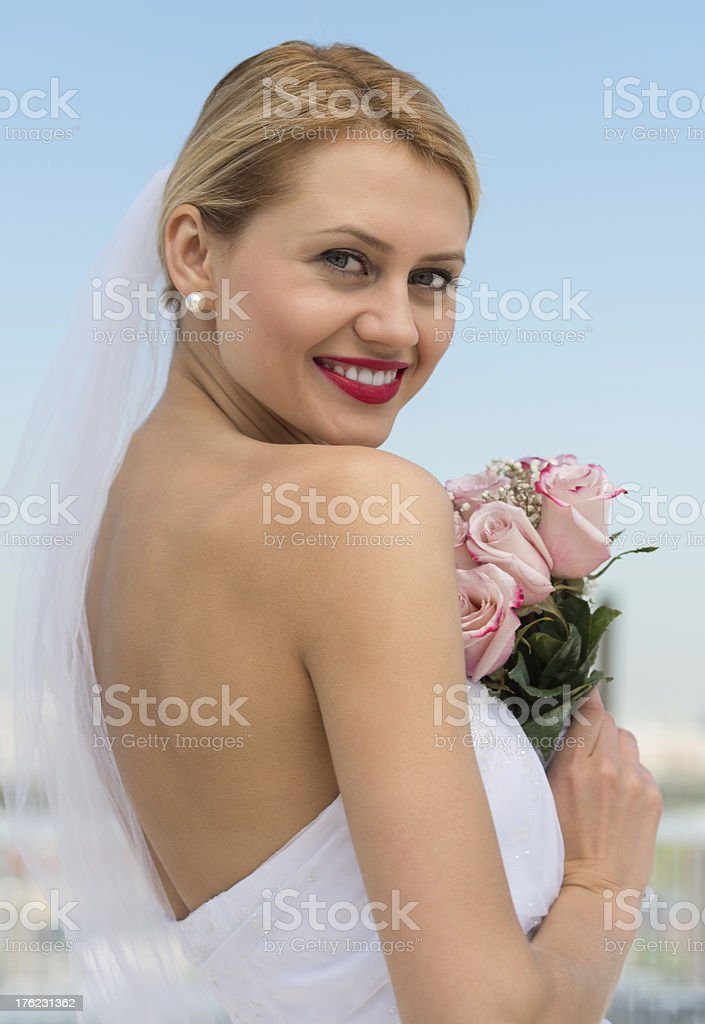 Beautiful Bride Holding Flower Bouquet Against Sky stock photo