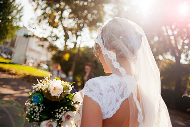 beautiful bride holding flower bouquet - veil stock pictures, royalty-free photos & images