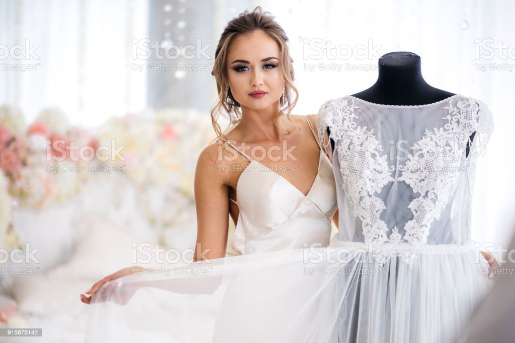 ab24a50d01d A Beautiful Bride In A Silk Night Dress Shows Her Wedding Dress In ...