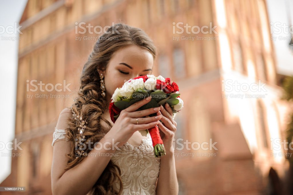 Beautiful Bride In A Wedding Dress With A Braid Hairstyle Sniffing