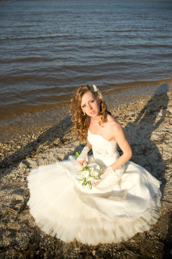 674214372 istock photo Beautiful bride in a white dress on coast of river 488910231