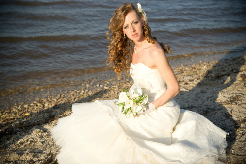 674214372 istock photo Beautiful bride in a white dress on coast of river 488913759